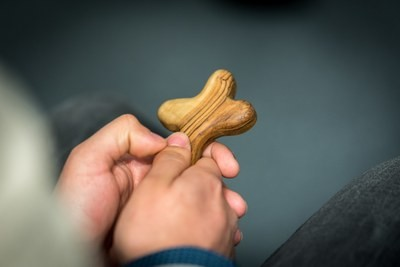 A person holds a cross in their hands.