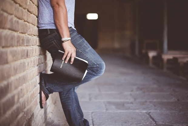 A man leaning against the wall with a Bible in his hand
