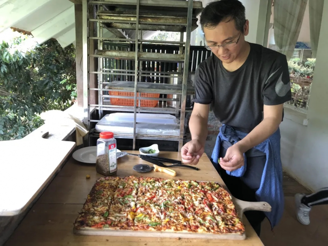 A volunteer from Guangxiao Church in Guangzhou made a big pizza for youths with intellectual disabilities in Huiling Farm on March 28, 2021.