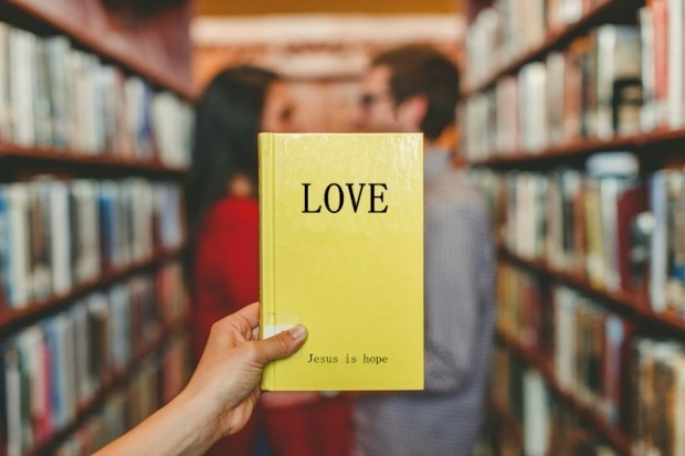 """A book named """"Love"""" in front of a couple"""