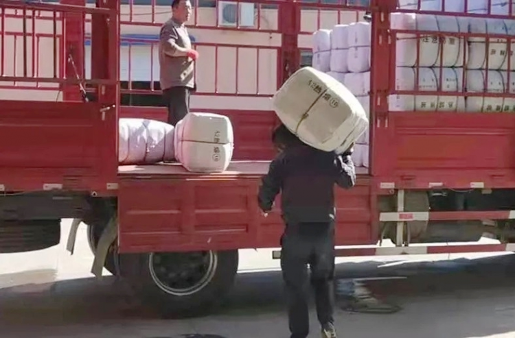Volunteers of the Amity Foundation loaded quilts which were to be delivered to flood-hit Songgu Township, Jiexiu City, Jinzhong City, on October 11, 2021.