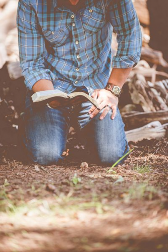 A man reads the Bible on his knees.